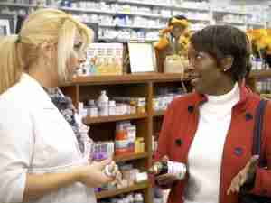 A woman discussing supplements with a pharmacist.