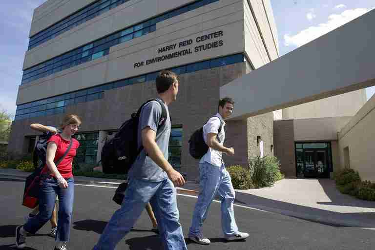 Three students walk past the Harry Reid Center building